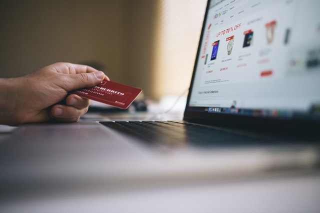 A person looking at an online shopping site and holding a credit card.