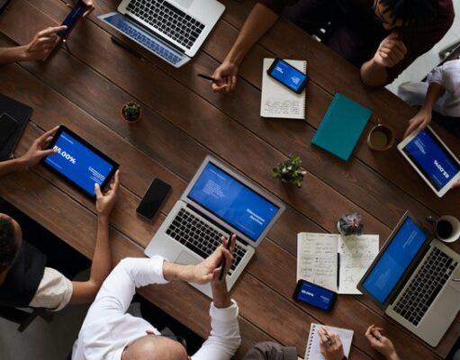A group of people sitting at a table with their laptops, tablets, and phones, symbolizing reasons to include social seeding in your marketing strategy.